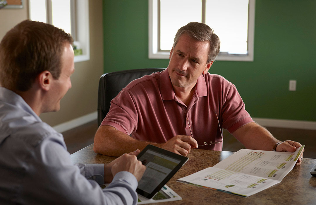 A Channel Seedsman is explaining Financing to a grower in an office.