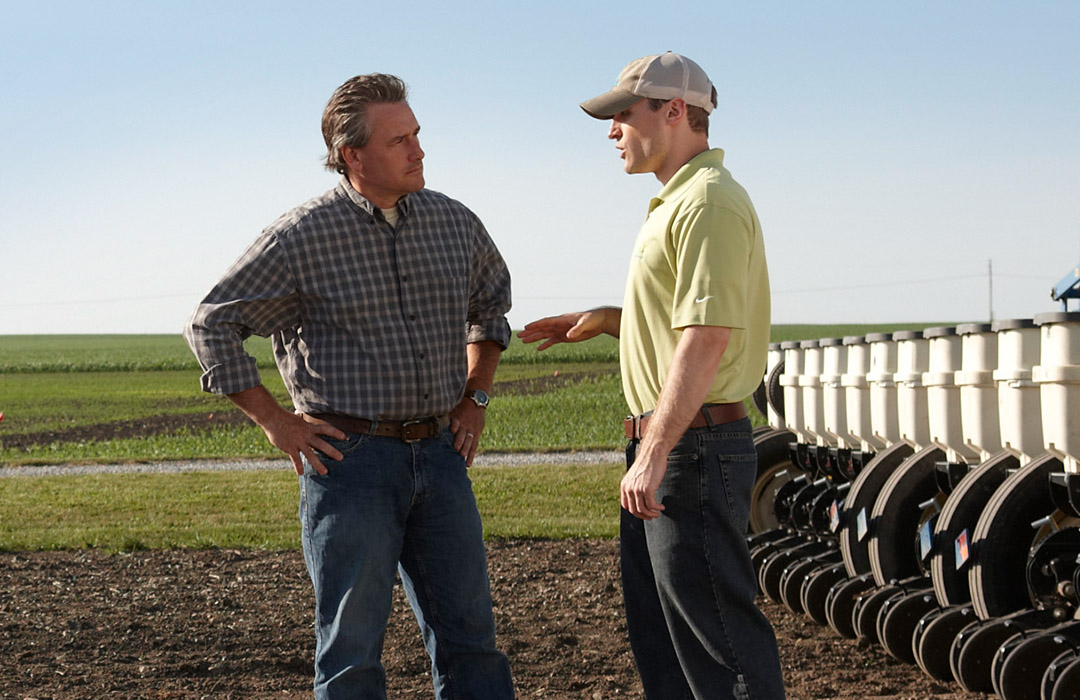 A Channel Seedsman and a grower talk in front of a planter in a field.