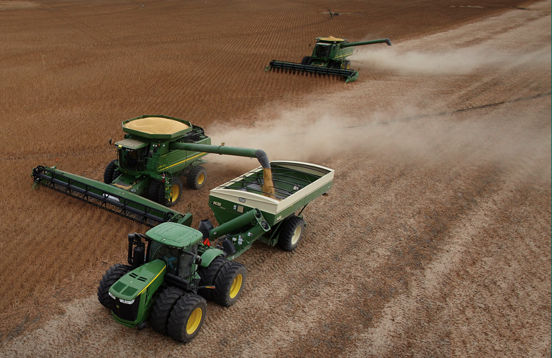 Channel products are harvested by two combines and a tractor.
